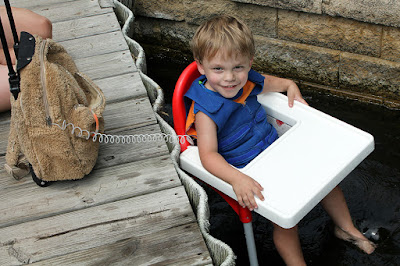 Boy in a highchair in the water wearing a cool kids toddler cooling vest