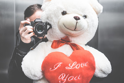 Getting engaged is one of the most joyful and happiest moments you will experience in your life - engagement tips - man with teddy bear and camera - Wedding blog - Weddings by K'Mich - Wedding planners - Philadelphia PA