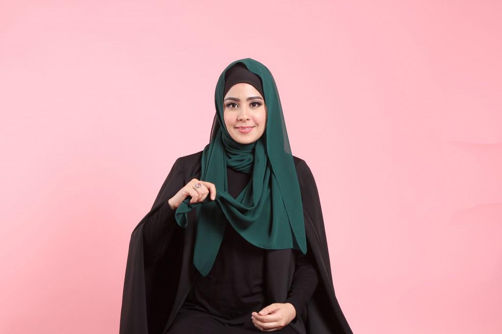 Langkah keempat ambil sisi pashmina yang bagian kiri ke arah depan dengan tangan bagian kanan. Pegang ujung dari jilbab pada sisi kiri. senyum manis