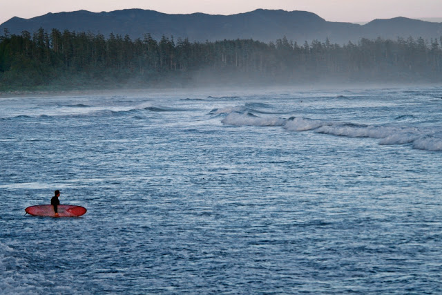 A lone surfer heads out at dusk...