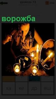 За столом в темноте при освещении свечек женщина занимается ворожбой с зеркалом