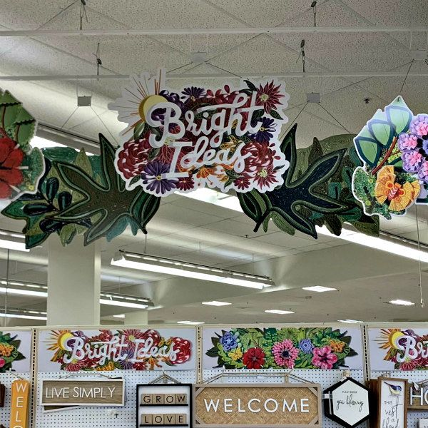 quilled floral signs hanging in a store and on pegboards