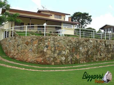 Muro de pedra construído com pedra moledo para formar o platô para a construção da piscina.