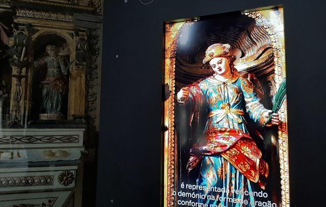 imagem de santa em tela de computador e num altar barroco