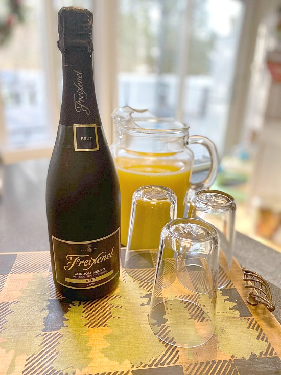 bottle of champagne and glasses filled with orange juice
