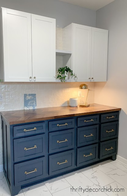 Dark blue cabinets, wood counter, cream shiny tile