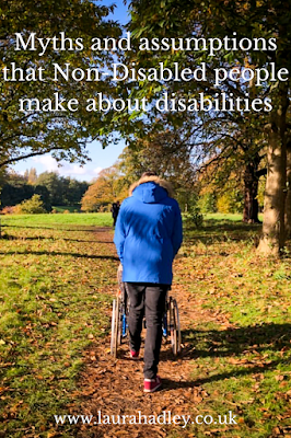 A man called Andy who is wearing a sky blue parka and dark jeans is pushing his partner Laura (me) in a wheelchair. Laura is covered by Andy as the perspective is from behind him.We are in Sefton Park in Liverpool in the midst of autumn. There are autumn leaves on the paths and green space. It is a lovely day.