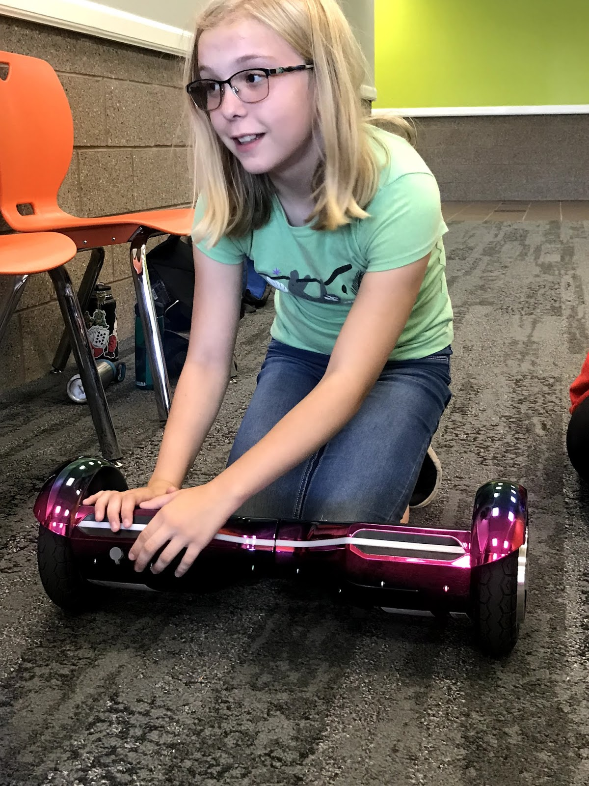a female student kneels down and checks out a hoverboard
