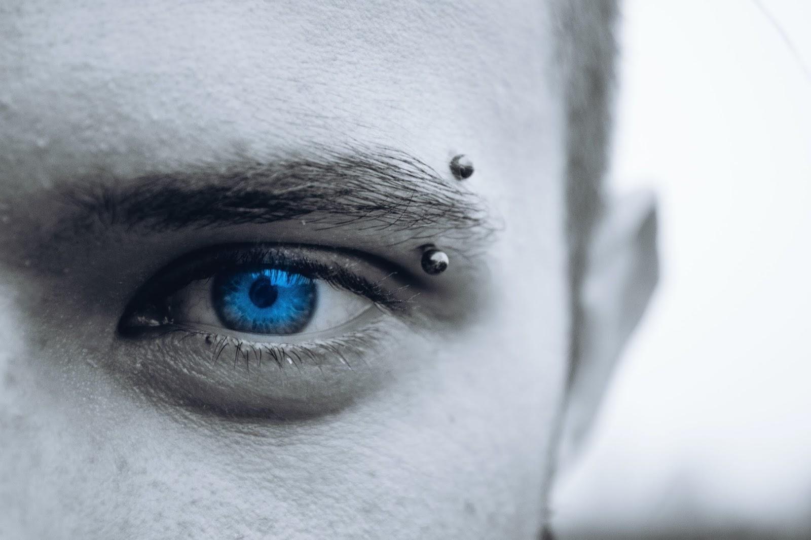 piercing al sopracciglio foto in bianco e nero e occhio blu
