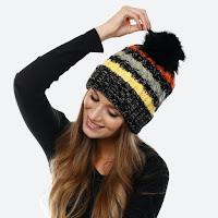 grey thick and cozy winter hat with yellow, grey, and red stripes and a big pompom
