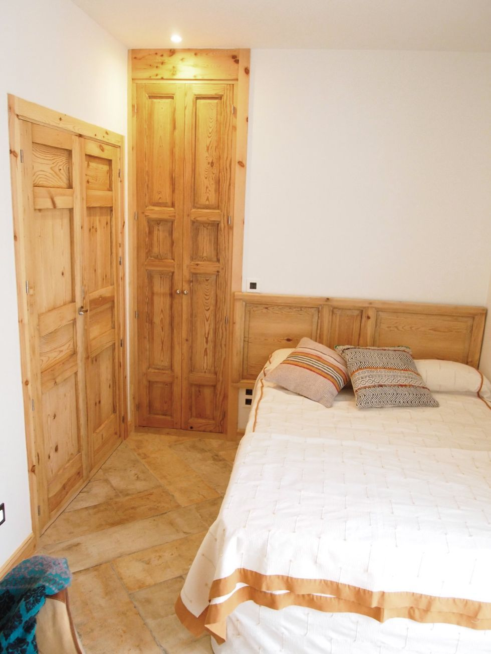 Dormitorio de estilo vintage con puerta recuperada como cabecero de cama