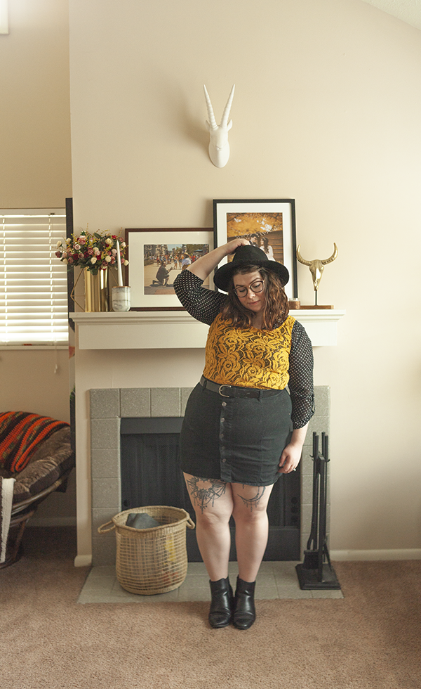 An outfit consisting of a black wide brim fedora, a black and white dotted 3/4 sleeve blouse layered under a yellow lace tank top, tucked into a black button up mini skirt and black Chelsea boots.