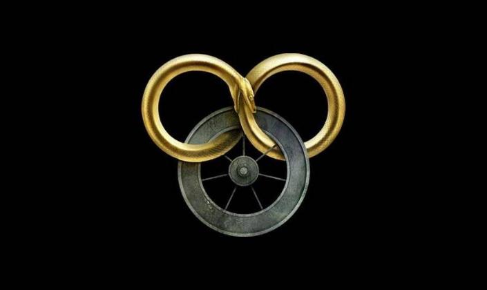 Imagem de capa: fundo preto com uma serpente dourada formando um 8 ou um símbolo do infinito ao morder sua própria cauda, e em sue corpo está enrolada um círculo de ferro trabalhado com aros saindo a partir do centro, literalmente uma roda.