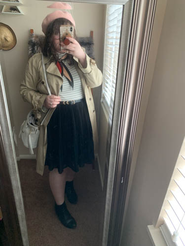 A mirror selfie of an outfit of a pink beret, khaki trench coat, white turtleneck shirt, pink red and black neck scarf, black pleated skirt and black Chelsea boots.