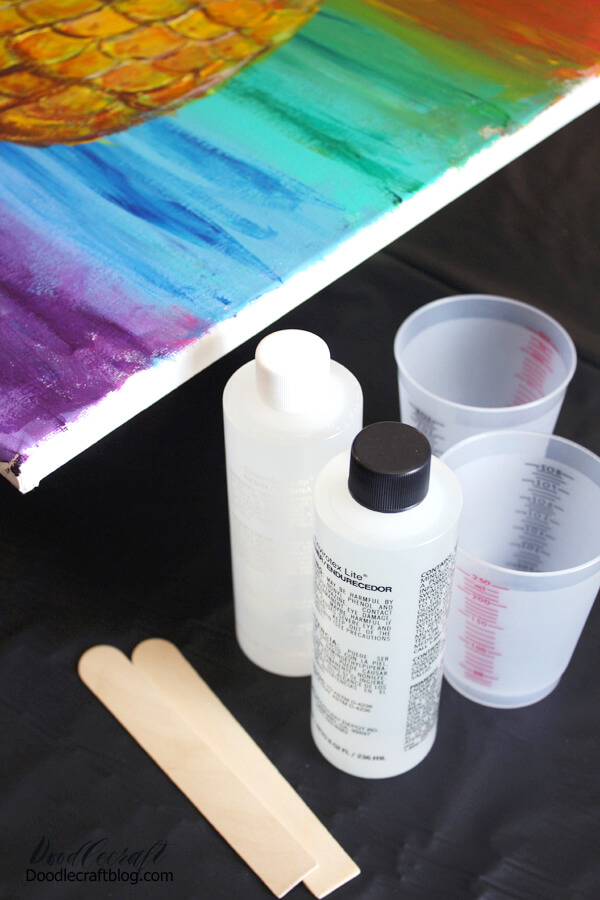 Begin by placing the canvas in the cardboard box, raised up on paper cups. Or place the cups and canvas on a disposable work surface. If the canvas is in the box, it can be closed to prevent dust, hair or bugs from landing on it.