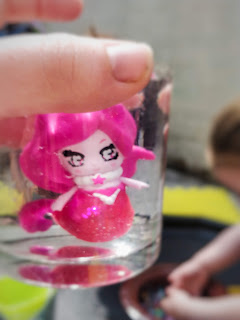 A glass of clear looking liquid is held up with a pink mermaid visable surrounded by very faint clear round orb shapes. You can see a small girl playing in the background which is blurry and focused onto the glass.