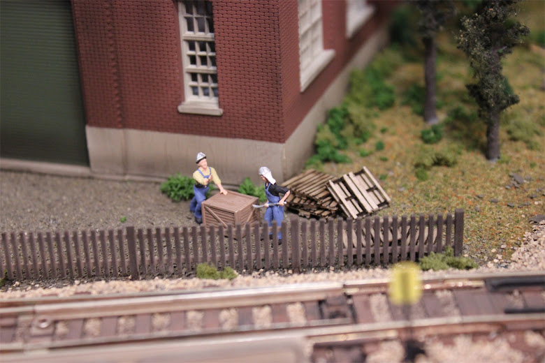 Dock workers opening a wooden crate alongside a brown picket fence and railroad track