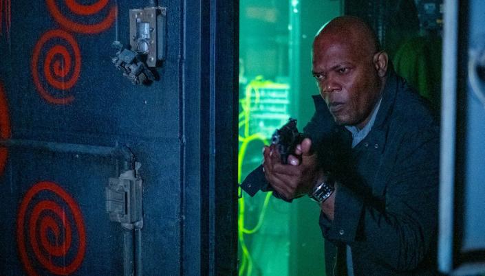 Imagem: o personagem do Samuel L. Jackson com um révolver em mãos invadindo uma sala escura com uma porta azul velha e espirais vermelhas pichadas nela.