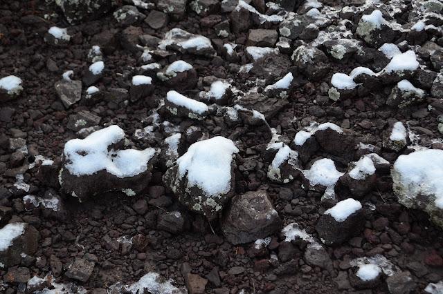 a little snow on black rocks