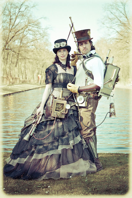 Steampunk couple (man and woman) at elf fantasy fair (elfia) wearing a dress, top hat, goggles, backpacks and weapons.