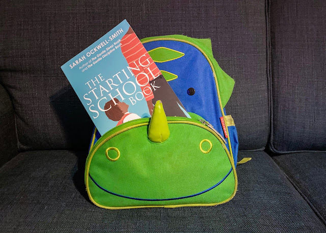 A dinosaur school bag with a teal book sticking out of it. The book is called the starting school book by Sarah Ockwell Smith providing information about how to choose schools, how to prepare and how to settle