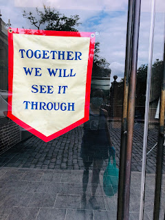 "My reflection in a glass door that has a sign that says ""Together We Will See It Through."""