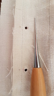 awl on a piece of a white linen edwardian corset
