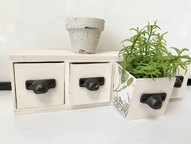 set of drawers with plant and pot