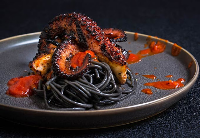 Grilled Octopus Over Squid Ink Pasta and Tomato Garlic Sauce
