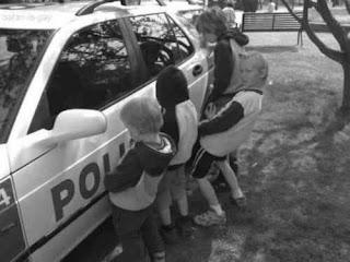 cuatro niños orinando contra la puerta de un patrullero