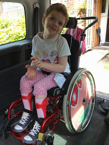 Picture of Daisy in her wheelchair in the back of her wheelchair van. She is smiling and happy , on her way to school