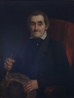Painting of a old white man dressed in black, sitting in a red chair, holding wooden tools used boat building.