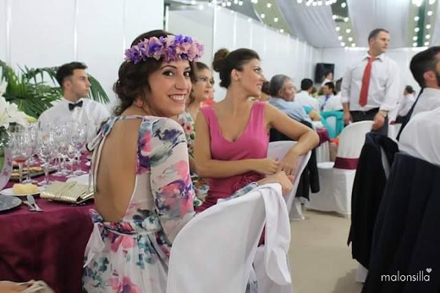 La invitada sentada a la mesa de la boda con el vestido de escote en la espalda y corona de flores lila