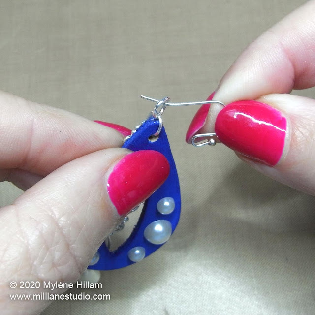 Inserting the earring wire through the jump ring at the top of the earring.