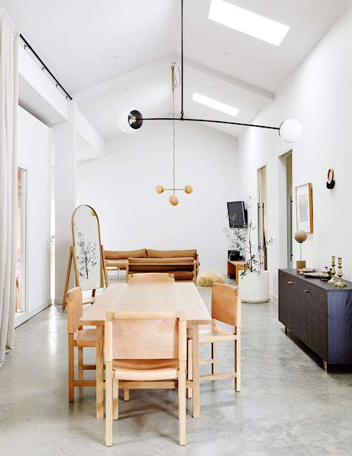 light wood dining table with simple wood chairs with cognac leather seats, modern hanging geometric linear lights with globes
