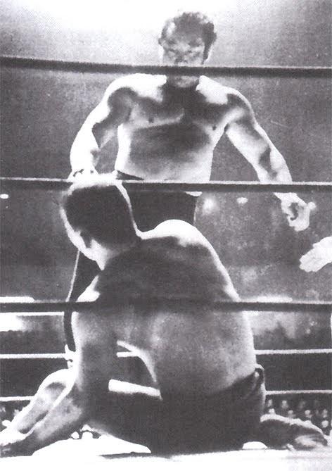 プロレスのリングのロープ際で木村政彦が倒されて力道山が立っている