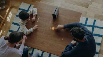 Sebuah keluarga sedang bermain game di atas meja memanfaatkan proyektor cerdas Sony Xperia Touch (blogs.sonymobile.com) updetails.com