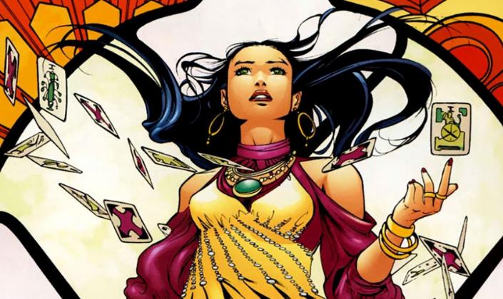Imagem de capa: uma ilustração dos quadrinhos da personagem Madame Xanadu, uma mulher de cabelos negros com uma roupa amarela com mangas arroxeadas, longos cabelos negros, ao redor de cartas flutuando ao redor e um fundo de vitral com amarelo e laranja e branco.