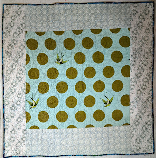 Three light blue fabrics with circular printing create the quilt back.