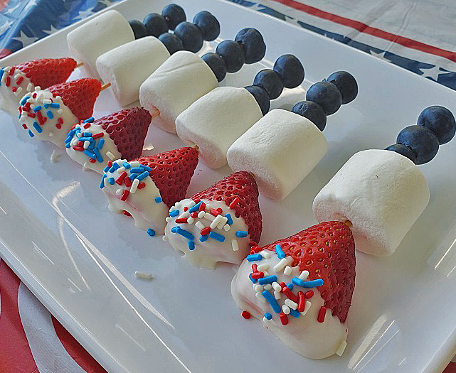 these are red white and blue fruits and marshmallows to celebrate a patriotic food party. Blueberries, strawberries dipped in white chocolate were used on a white plastic plate