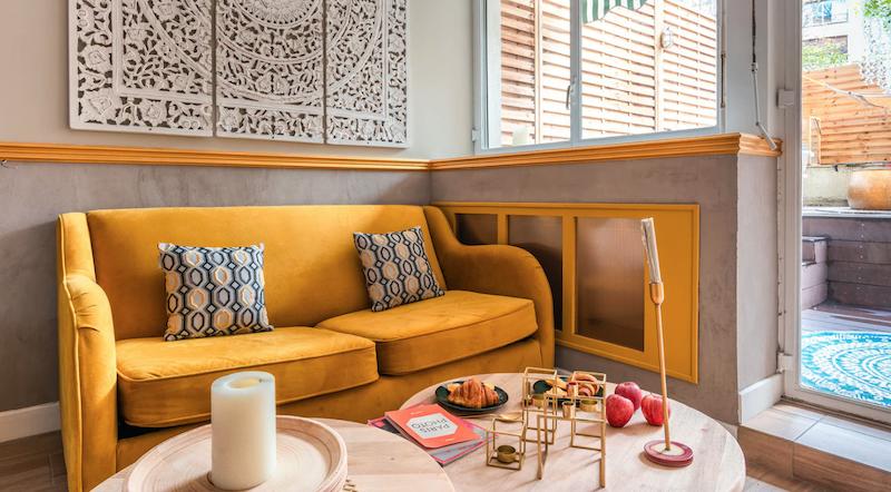 Sofá con funda dorada en salón de estilo chic