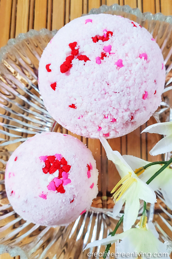 Learn how to make easy DIY bath bombs with essentials oils that smell like candy hearts! These step by step instructions and video makes it simple for beginners to learn how to make bath bombs to give as gifts, keep or to sell. You'll love using natural ingredients like epsom salt to get a Lush quality bath bomb for a lot less money.