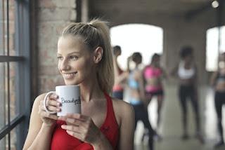 wanita minum kopi sebelum olahraga