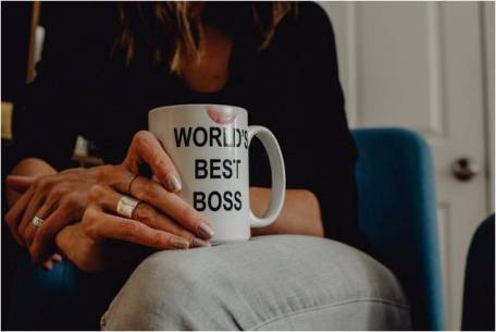 A woman holding a worlds-best-boss coffee mug, representing women in business