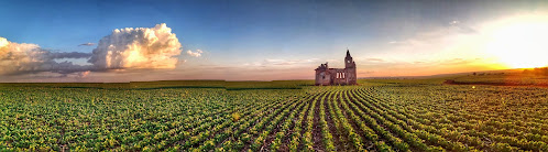 An old brown church in a field of green plants in red dirt at sunset. Unnamed Road,Palmital, Brazil. Photo by Sergio Souza