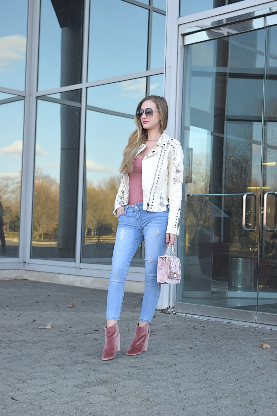Wearing Blank Ivory Vegan Floral Embroidered Moto Jacket, Rose colored basic body from forever21, wearing Steve madden cythiav pink velvet booties, Wearing pink velvt chain purse, Express mid rise distressed jeans, spring leather jacket look