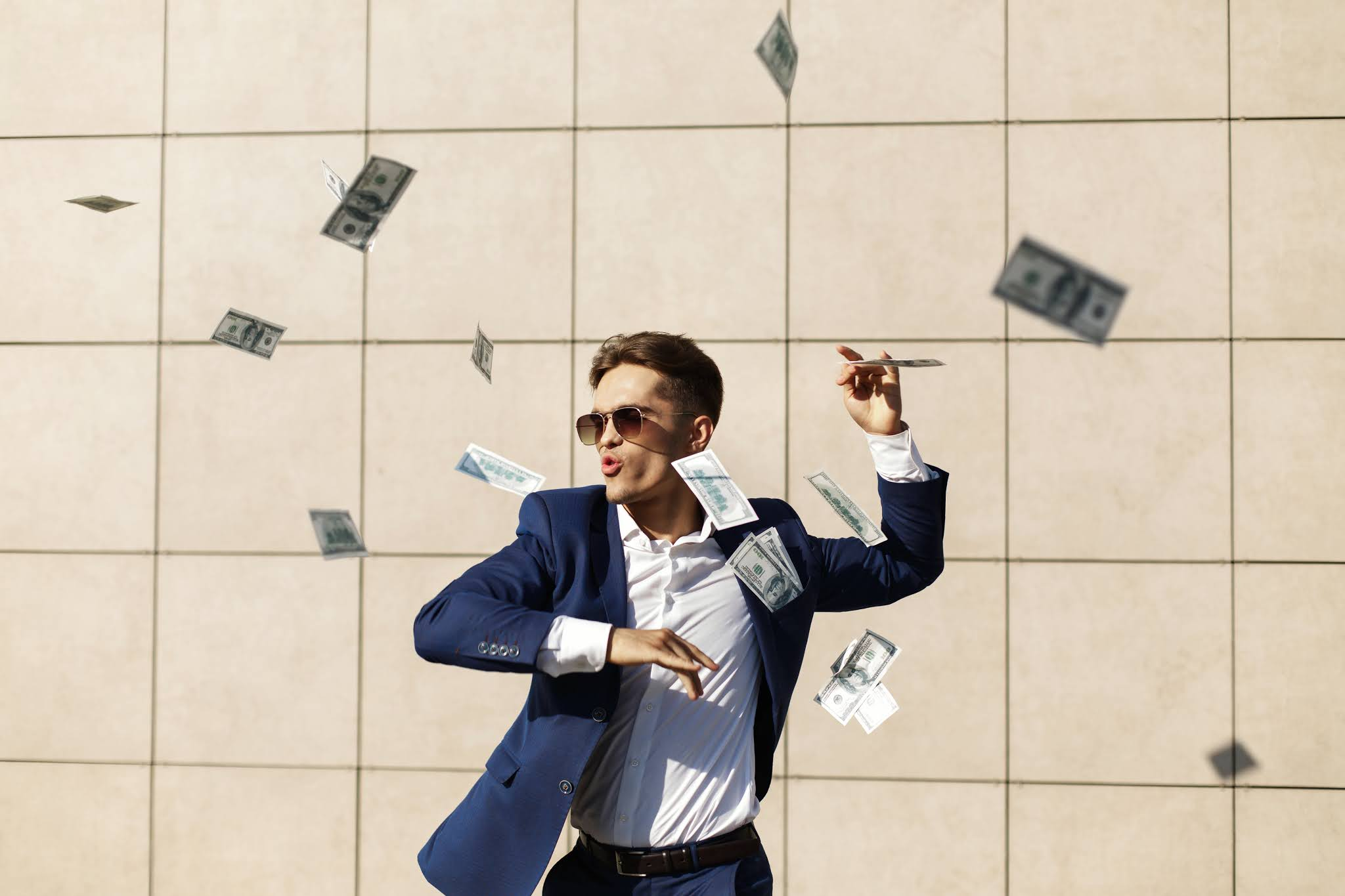 young businessman throughs around dollars dances street min