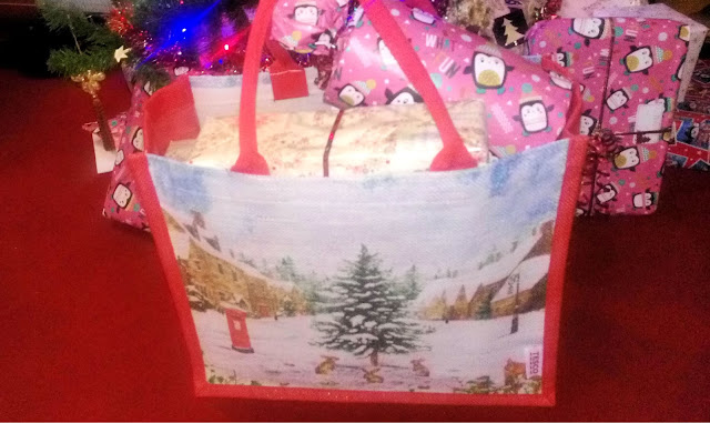 A tote bag with a snowy scene on the front, full of gifts under a Christmas tree.