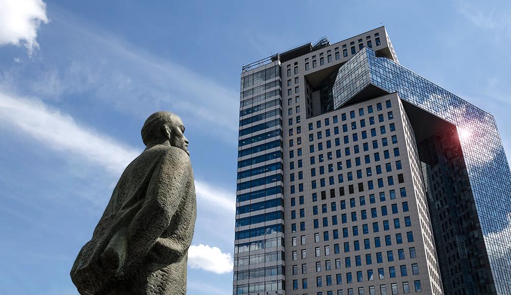Altes Lenindenkmal vor einem neuen Bürohochhaus in Moskau