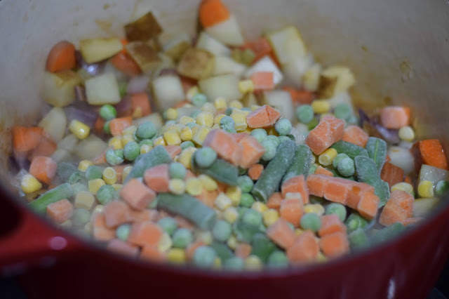 The frozen vegetables being added to the pot.